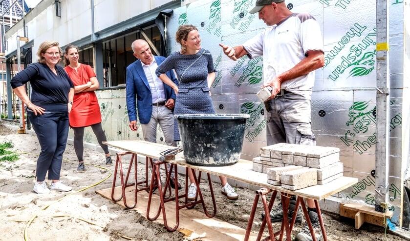 Een vakman geeft huisartsen Petra Gerritsen, Sabine Janssen en Gerjo Steeneveld (v.l.n.r.) en fysiotherapeut Ton van Walstijn (derde van links) uitleg over het metselen. Foto: Luuk Stam