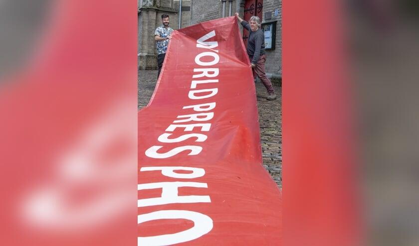 """De banner ligt uitnodigend als een rode loper voordat hij aan de gevel van de Walburgiskerk wordt bevestigd. """"World Press Photo is voor de zesde keer in Zutphen. Normaal gesproken is de tentoonstelling wereldwijd in negentig steden te zien. Nu slechts in negen steden, waarvan Zutphen er  één van is. We hebben geluk dat de Walburgiskerk de ruimte biedt."""" Links Patrick van Gemert en rechts Arjen Woudenberg, inspirators en organisatoren van het eerste uur. Foto: Gerard Mühlradt"""