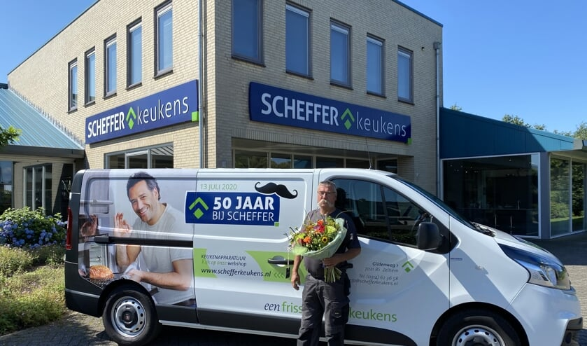 Jubilaris Bennie Massen 'poseert' met een bos bloemen voor zijn bus, die voor dit jubileum wat aangepast is. Foto: PR