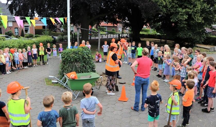 Directeur Dicky ter Beek samen met 'Opa Harrie' omringd door de kinderen van de Antoniusschool tijdens de aftrap van het groene schoolplein-project. Foto: Antoniusschool Vragender