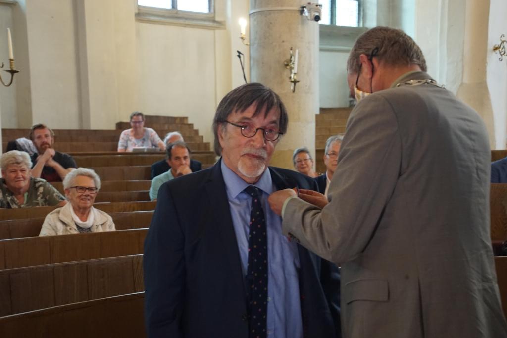 Herman Onnink krijgt de Koninklijke onderscheidinh opgespeld. Foto: Frank Vinkenvleugel  © Achterhoek Nieuws b.v.