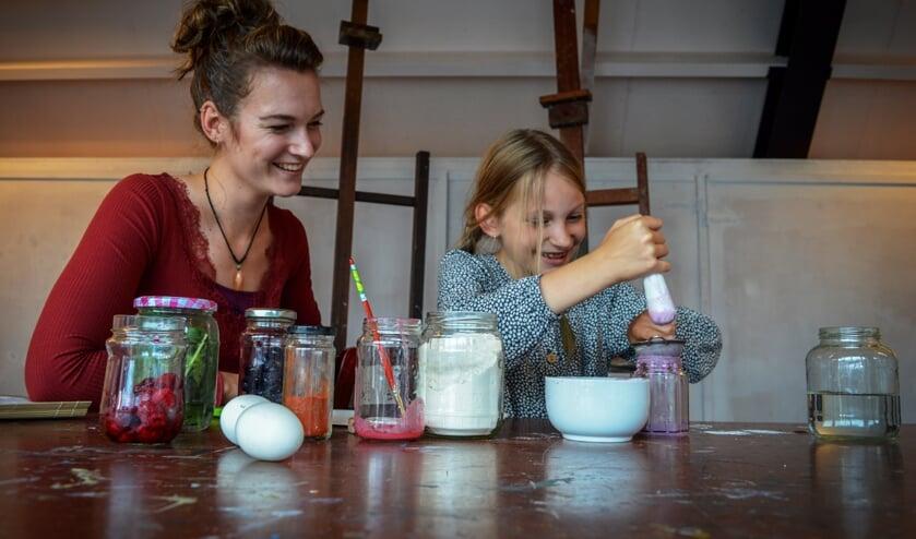 Fenna Houtman maakt zelf verf van natuurlijke materialen onder toeziend oog van Jolien Visser. Foto: Miranda Visser.