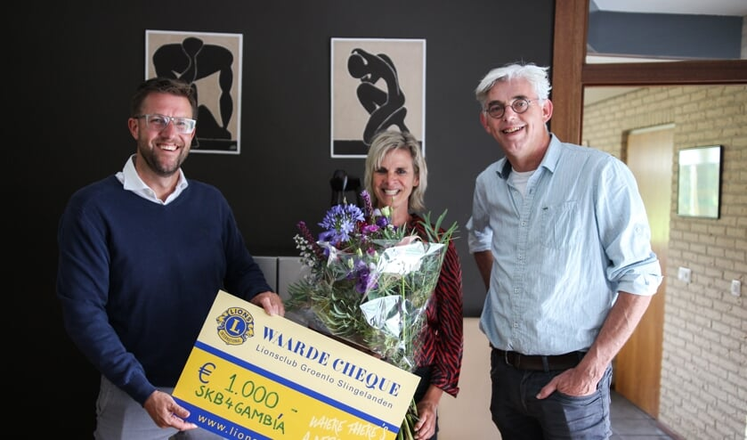 Carla Klein Breteler van SKB4Gambia (midden) krijgt de cheque behorend bij de Lions Award uitgereikt door president Maarten Reimes (links) en lid Theo Helmers (rechts) van de Lionsclub Groenlo-Slingelanden.
