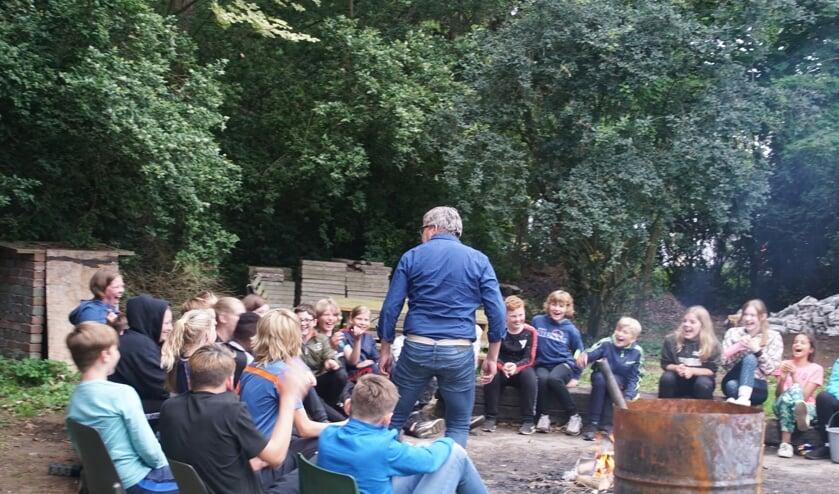 Meester Jan vertelt een spannend kampvuurverhaal.  Foto: Frank Vinkenvleugel