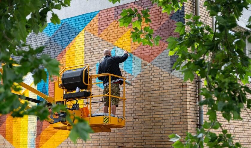 De street art artist Mr. June werkt aan zijn kunstwerk op de muur van de 'stenen gymzaal'. Foto: Rick Mellink