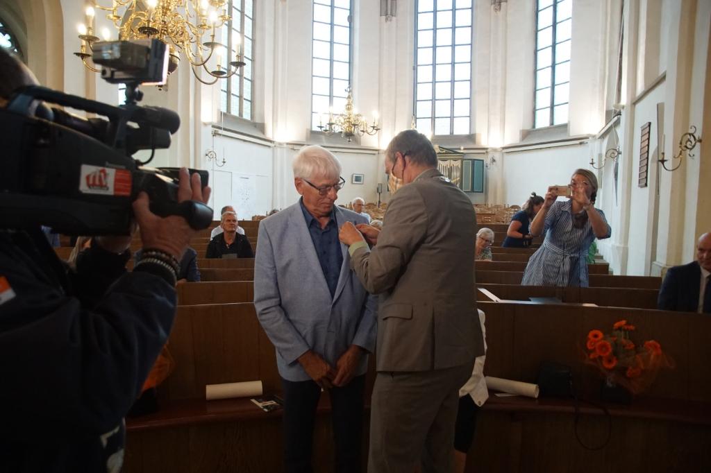 De burgemeester speldt de versierselen op bij Dick ter Maat. Foto: Frank Vinkenvleugel  © Achterhoek Nieuws b.v.