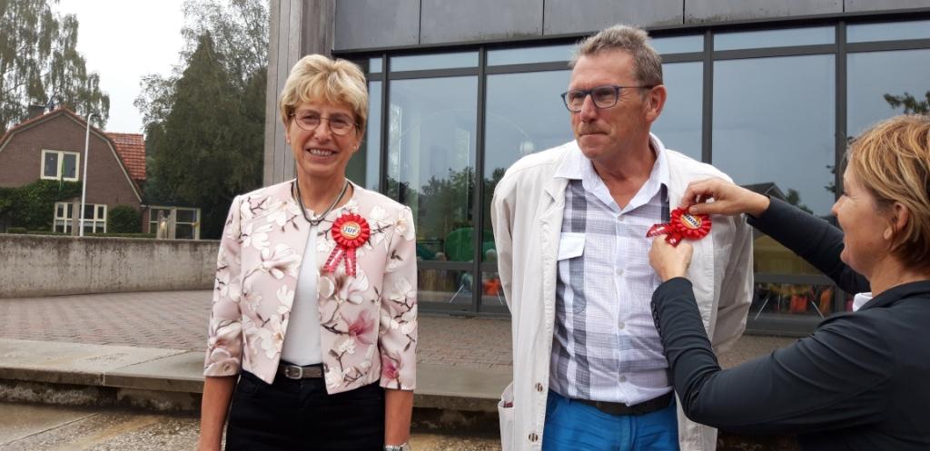 Directeur van De Hoge Voorde Hennie Gesthuizen speldt Anja en Gerard de versierselen op. Foto: Leidienke Elsman  © Achterhoek Nieuws b.v.