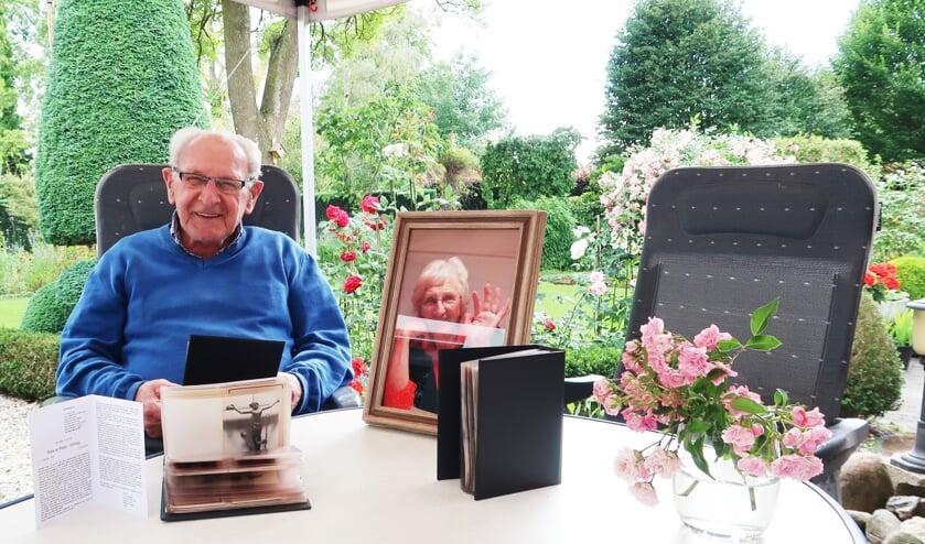 Tonnie te Plate, zittende in zijn eigen fraaie achtertuin met naast hem de foto van vrouwlief Riek. Foto: Theo Huijskes