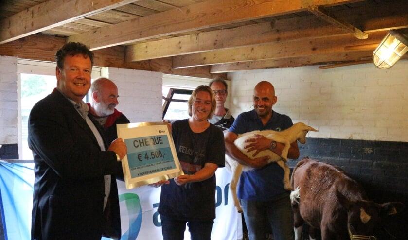 Erwin van Tienoven van Amcor overhandigt de cheque aan Cynthia Imhoff (vervangend beheerster van de Schouw). Een medewerker van Amcor, Massimo Scanu, houdt de geit vast. De heren achteraan zijn cliënten van Zozijn, samenwerkingspartner van de kinderboerderij. Foto: PR