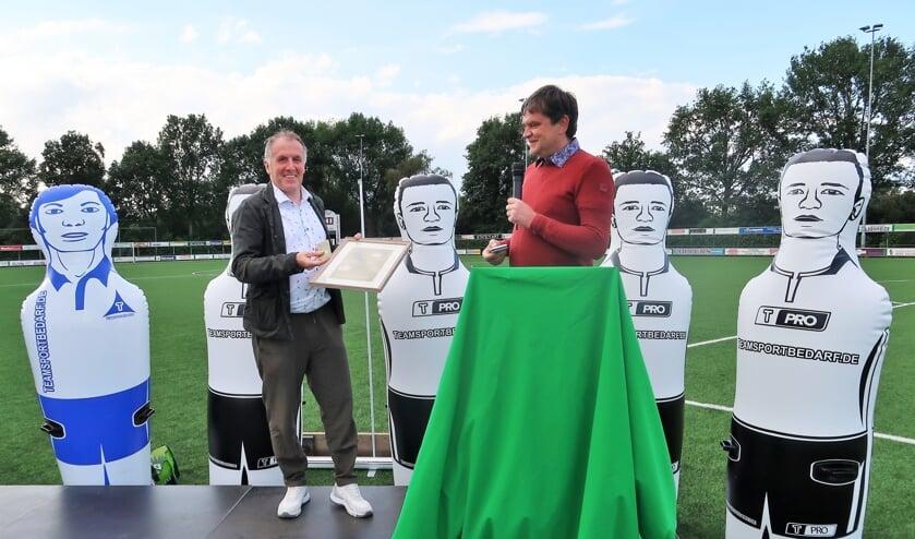 RKZVC-voorzitter Johnny Cuppers overhandigt scheidend trainer Laurens Knippenborg een gouden seizoenkaart voor het leven. Foto: Theo Huijskes