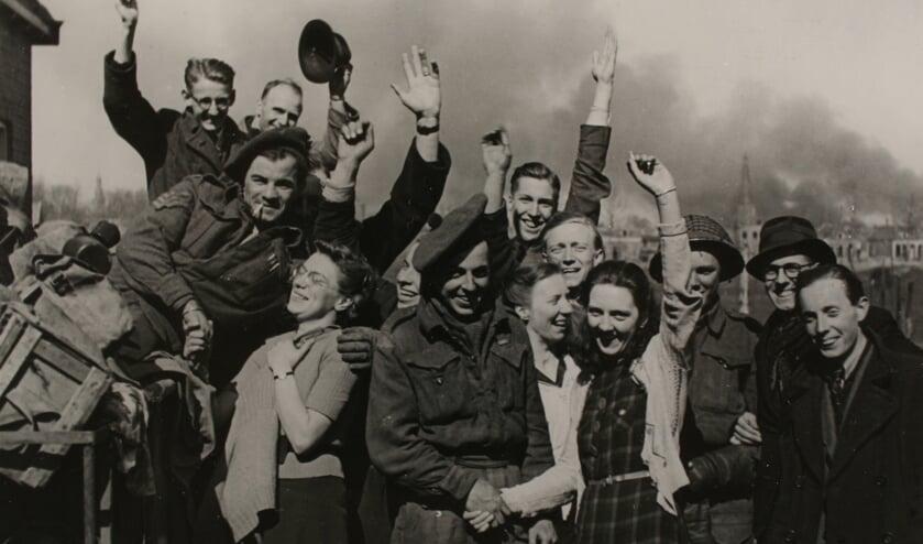 Zutphen na de bevrijding in 1945: een groep feestende burgers rond enkele Candadese militairen met op de achtergrond de brandende Nieuwstad met de St. Jan. Foto: Stedelijk Museum Zutphen