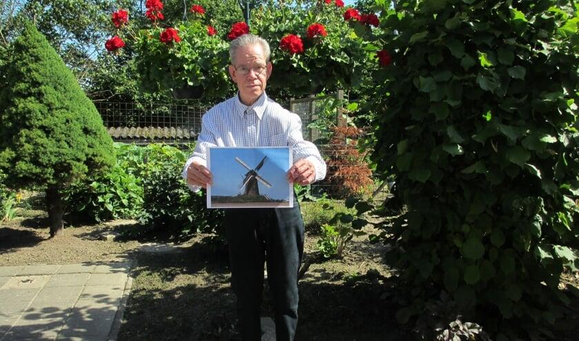 """Wim Knaake met een foto van zijn favoriete plek in Bronkhorst: de molen. """"Vroeger met Pasen gingen we daar eieren rollen.  Dan klommen we bovenop de molenbult en rolden we eieren naar beneden."""" Foto: J.E. Aalderink-Wolters."""