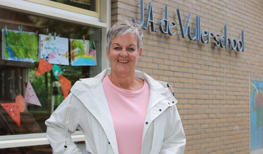 Juf Trudy, voor het raam van haar klaslokaal, neemt vrijdag afscheid. Foto: Arjen Dieperink