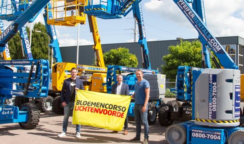 Wesley Helmers en Kevin Stöteler van Pfeifer Machinery en Herman ter Haar (midden) poseren met de corsovlag na het ondertekenen van het sponsorcontract. Foto: PR Stichting Bloemencorso Lichtenvoorde