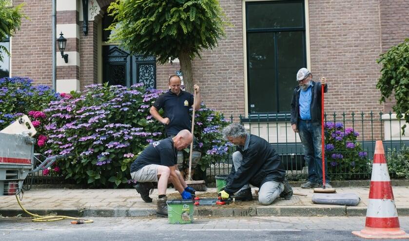 Eén van de tegels wordt gelegd door Henk Greven (l) en Harold Pelgrom. Op de achtergrond Joey Mullink en Harry Jansen. Frank Sessink ontbreekt op de foto. Foto: Anka Pelgrom