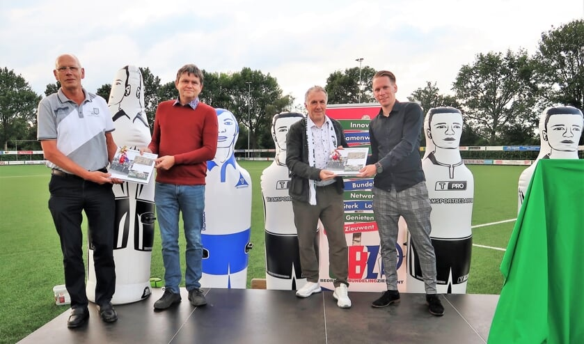 De overhandiging van het jubileumboek aan voorzitter Johnny Cuppers door Bennie Storkhorst (links) en aan trainer Laurens Knippenborg door Sjors Storkhorst (rechts). Foto: Theo Huijskes