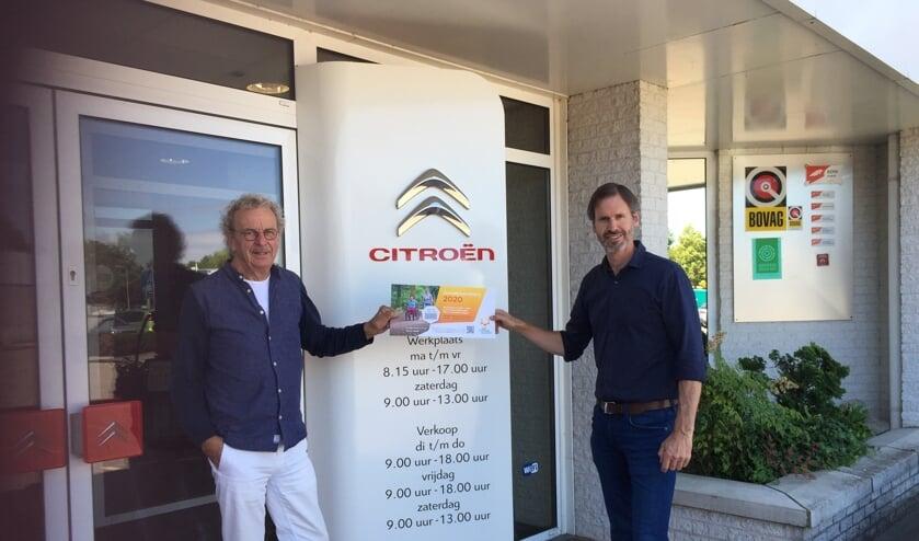 René Ruesink (r), mede directeur van Autobedrijven Ruesink gaf het startsein voor de Zonnebloemloten campagne door het kopen van het eerste Zonnebloemlot van de voorzitter Koos Luurs van de Zonnebloemafdeling Ruurlo. Foto: PR.