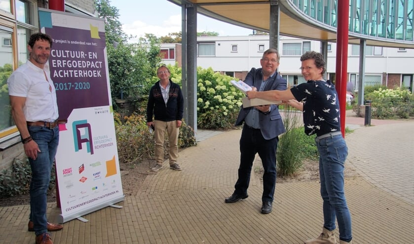 Joop Wikkerink overhandigt de Beeldende Box aan Karin Droppers. Werner Menkehorst, assistent regio manager Careaz (links) en Harry ten Brinke, projectleider kijken toe. Foto: Frank Vinkenvleugel