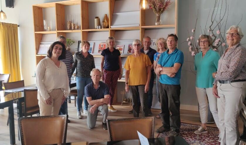 De leesclub Neede voor de boekenkast, met links Estrella van Liere en staand met de armen over elkaar Jaap Wolff. Foto: Rob Stevens