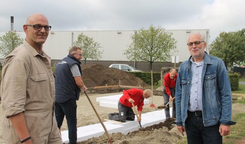 Rene te Selle (l) en Ben Aardeman kijken toe hoe de vrijwilligers de isolatie aanbrengen voor de toekomstige werkplaats. Foto: Lineke Voltman