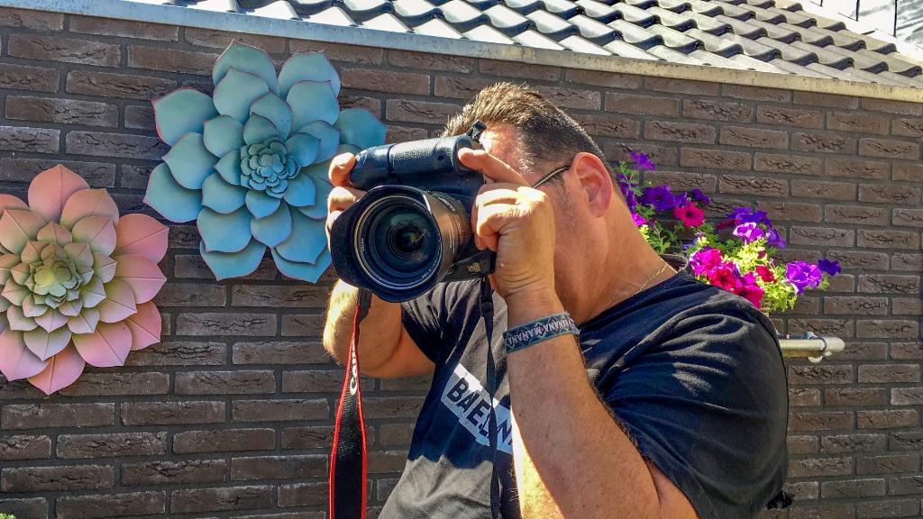 Fotograaf Albert Schreuder kantelt zijn camera voor een staande foto, stelt rechts scherp en drukt links af. Foto: Tamara Schreuder-Hissink  © Achterhoek Nieuws b.v.