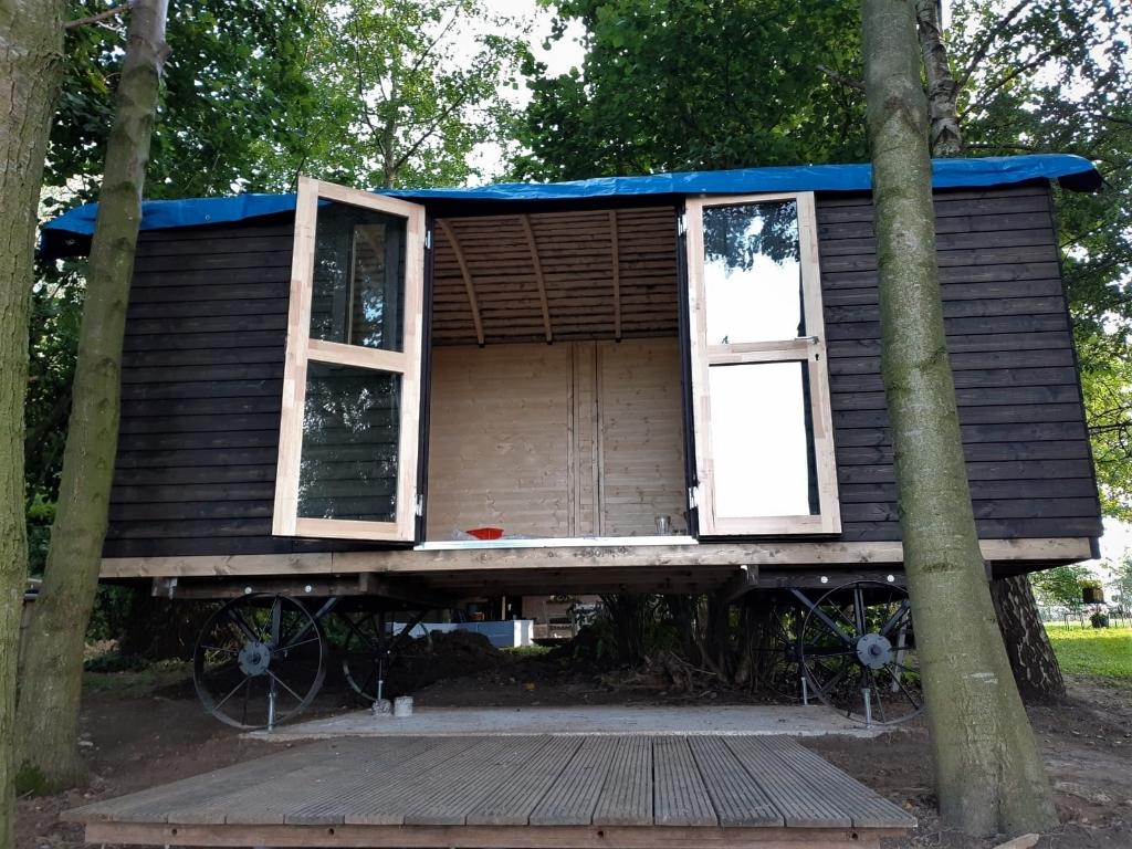 De werkzaamheden aan Tiny House on Wheels 'Into the Wild' zijn nog in volle gang. Op de voorgrond een houten terras voor het buitenzitje. Een trap voor de toegang moet nog gemaakt worden en aan de verdere binnenafwerking wordt de komende weken hard gewerkt. Foto: Alice Rouwhorst  © Achterhoek Nieuws b.v.