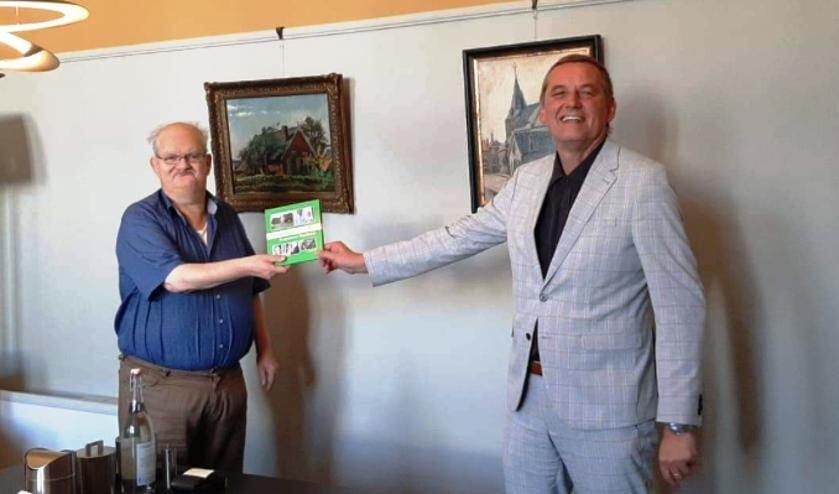 Leo van der Linde overhandigt het burgemeestersboek aan Anton Stapelkam. Foto: Communicatie gemeente Aalten