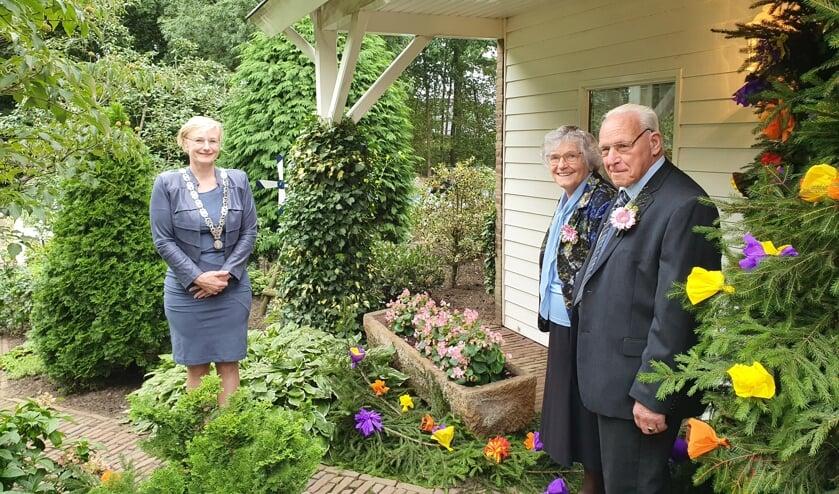 Burgemeester Marianne Besselink feliciteert Wim en Roelfine Onstenk op gepaste afstand. Foto: Familie Onstenk