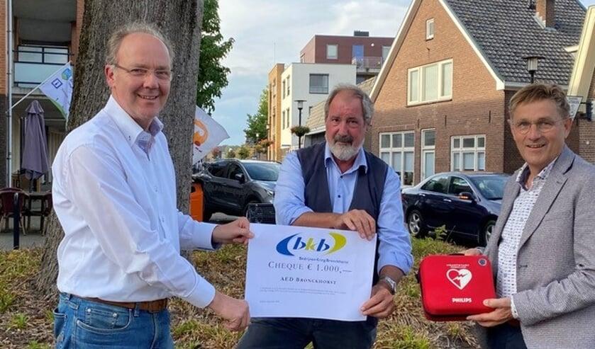 Pieter Gerrits overhandigt de cheque aan Johan van den Berg in het bijzijn van Herman Vrielink. Foto: PR