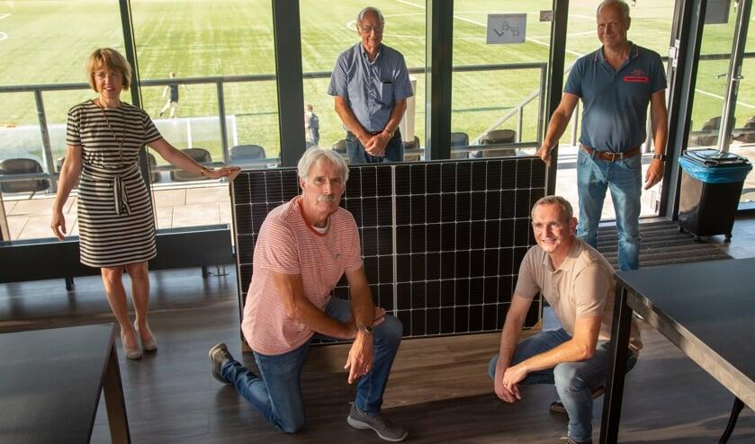 Wethouder Tineke Zomer, Hans Huls, Johan Mentink (staand van links naar rechts) en Gerrit te Kolste en Leon Klein Tank (knielend van links naar rechts) bij een van de zonnepanelen. Foto: Marco ter Haar