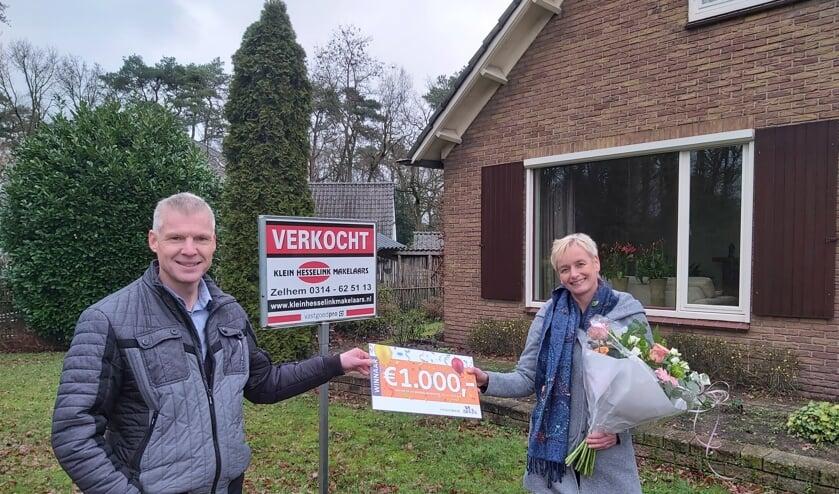 <p>Ellen Zemmelink ontving namens de familie, uit handen van makelaar Alfred Beeftink een cheque met de geldprijs. Foto: PR</p>