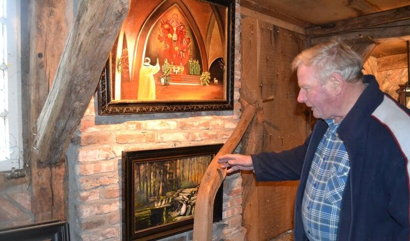 Herman Testerink in de schuur bij twee van zijn schilderijen. Foto: Karin Stronks