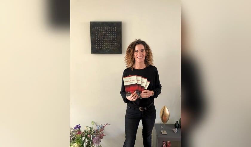 <p>Lot Rohde toont een aantal exemplaren van haar eerste bundel. Eigen foto</p>