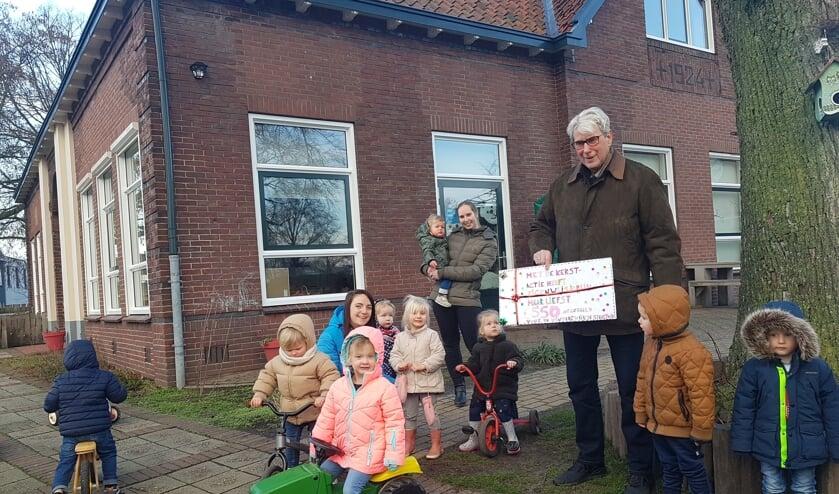 <p>De kinderen van Eigenwijsjerijk, samen met pedagogisch medewerkers Melanie en Ilse, geven een cheque aan en dhr. Vlam, interim-voorzitter van de Wijktuinen. Foto: Selma Hannink-van Ommen</p>