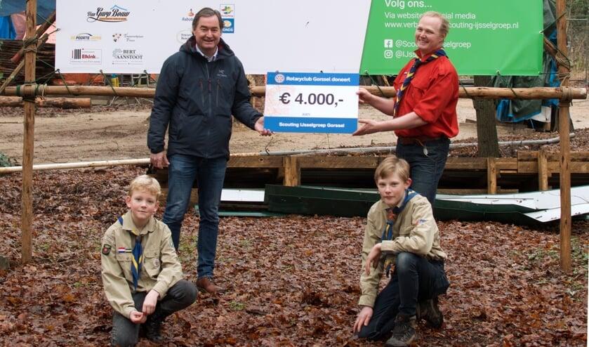 <p>Op de plek waar het nieuwe clubhuis komt overhandigt Joost Snoep (l.), voorzitter Rotary Gorssel, de cheque voor 4.000 euro aan enkele scouting jeugdleden en aan Niels Meijerink, voorzitter Scouting IJsselgroep Gorssel. Foto: PR</p>