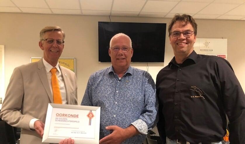 <p>Henk Mennink (midden) kreeg een gouden KNVB-speld voor scheidsrechters uitgereikt door KNVB-ambassadeur Henk Plas (l) in het bijzijn van voorzitter Henry Meutstege van VV Ruurlo. Foto: PR</p>