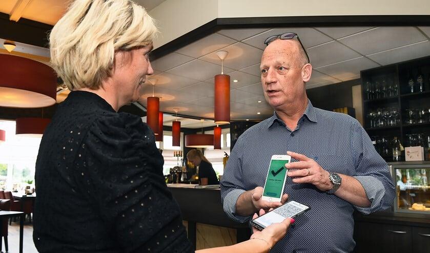 Carl Aalders van het Tolhuis scant een een corona-app. Foto: Roel Kleinpenning