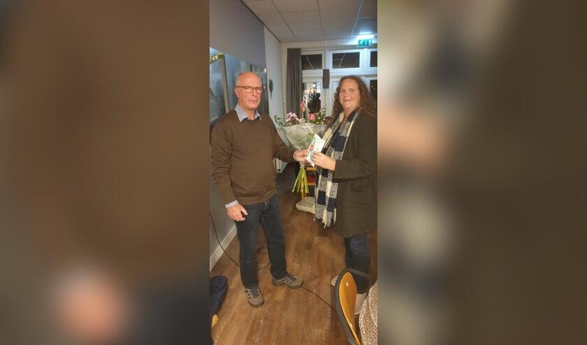 <p>Voorzitter Rigter overhandigt Maartje Hakze de bloemen. Foto: Erik Wildenbeest</p>