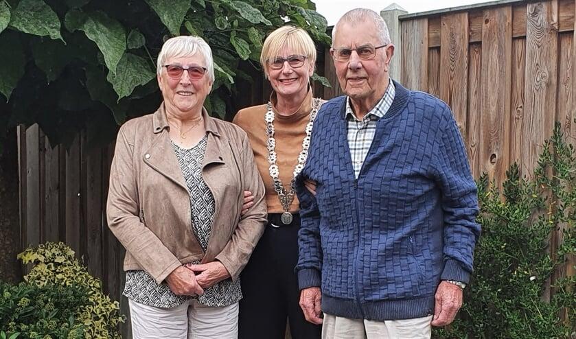 <p>Het diamanten echtpaar Mentink-Mulder poseert samen met burgemeester Marianne Besselink in hun achtertuin. Foto: Alice Rouwhorst</p>