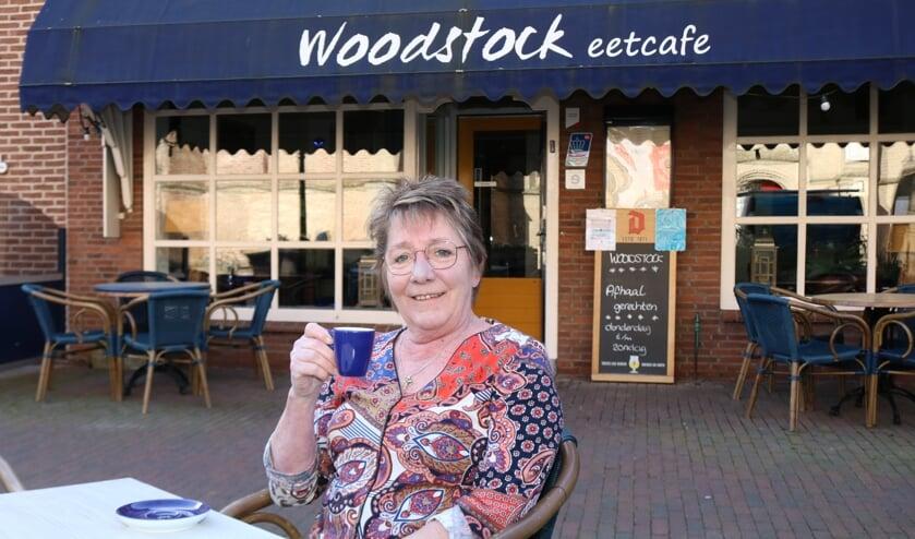 <p>Hendy Brinkert drinkt een kopje koffie op haar eigen terras. Ze vindt dat de terrassen weer open kunnen. Foto: Arjen Dieperink</p>