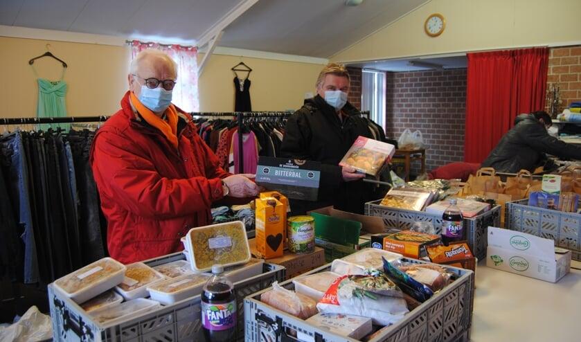 <p>Christiaan Makkinga en Dick de Waard met producten, die ze vrijdag naar de Voedselbank brachten. Foto: Contact</p>