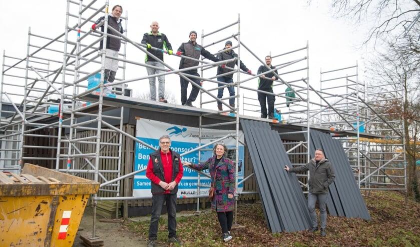 <p>Vrijwilligers van Zwembad Het Elderink en werknemers van De Variabele en Elro hebben de klus geklaard: een nieuw dak op het containerhok. Foto: Ellis Regina Photography</p>