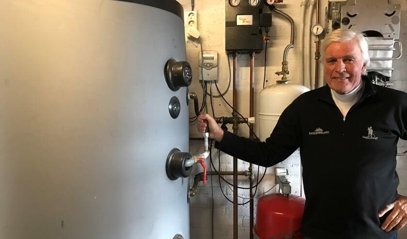 Martien Pater bij zijn voorraadvat voor 800 liter leidingwater dat met zonnecollectoren wordt verwarmd. Foto: eigen foto