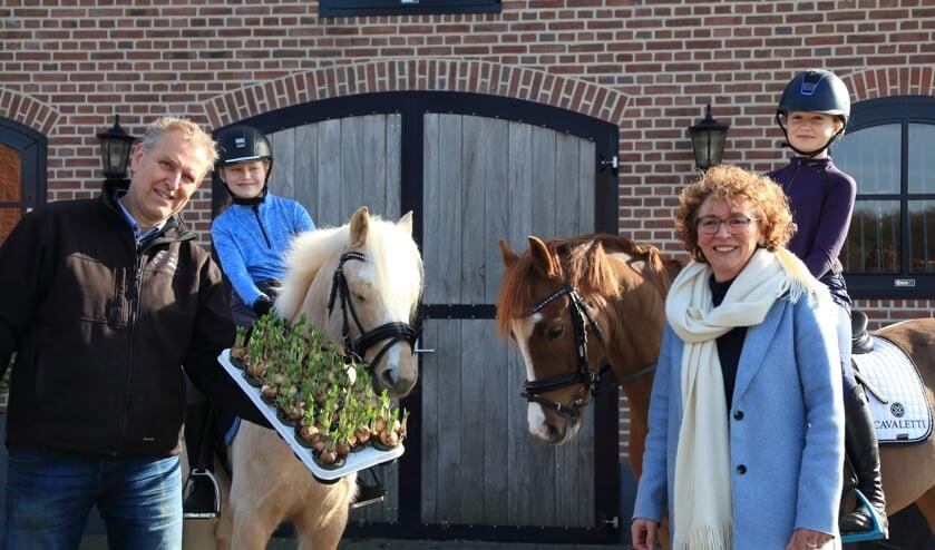 <p>Marco Groot Jebbink (links) levert de narcissen voor de clubactie. Verder op de foto voorzitter Gitte Wisselink en ponyclubleden Jet Gerritsen (links) en Levi Heusinkveld. Foto: Marije Stomps</p>