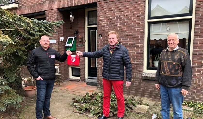 De overhandiging van de buurt-AED in de Kortestraat, van links naar rechts, initiatiefnemer Richard Oberink, Johan G. Esendam, voorzitter Hart4Winterswijk en Johnny Lens waar de AED hangt. Foto: Wim Kos.