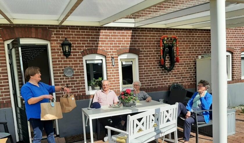 <p>Vrijwilliger Christien Kremer levert de verrassingsmenu's af bij het echtpaar Bussink, en hun gast mevrouw Lammers. Foto: H. Vriezen</p>