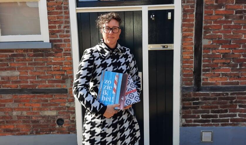 <p>Linda Commandeur met haar nieuwste boek. E&eacute;n exemplaar is alvast verpakt in het nieuwe Grolse Wanten-inpakpier. Foto: Kyra Broshuis</p>