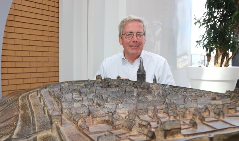 <p>Paul Roodbol bij het kunstwerk dat Lochem voor de stadsbrand in1615 weergeeft. Foto: Arjen Dieperink</p>