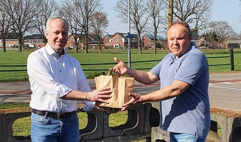 IKAD-Penningmeester René Ottevanger ontvangt een verrassingspakket van Martin Hüning, voorzitter van de lokale afdeling van KHN. Foto: PR