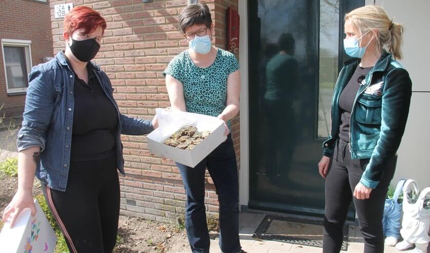 <p>Lobke van Bijzonder Gewoon (l) en Nicole Haarman van de Rotary overhandigen de brownies aan een medewerker van Marga Klomp&eacute; locatie Meddo. Foto: Lineke Voltman</p>